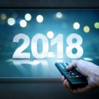 Hand holding remote control with 2018 on TV screen. Happy New Year 2018